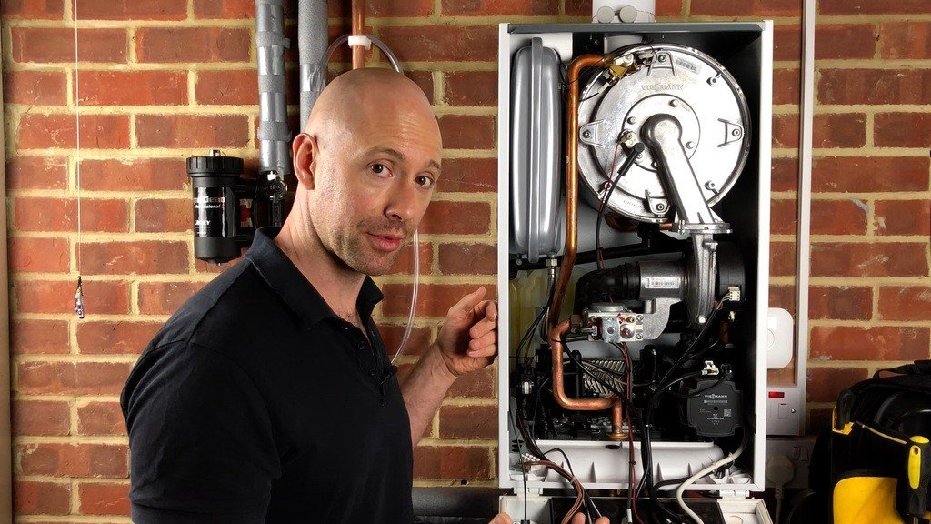 Photo of George the heating engineer standing by a boiler