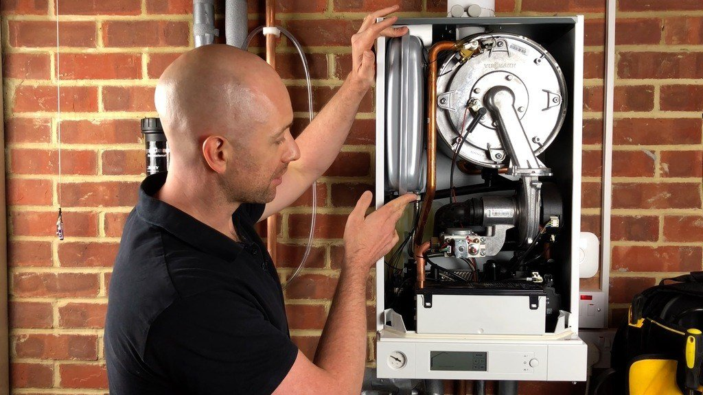 heating engineer looking at boiler